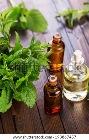 Essential aroma oil with peppermint  on wooden background. Selective focus, vertical. - stock photo