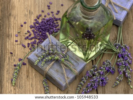 essential lavender oil and herbal soap with fresh flowers on wooden background - stock photo