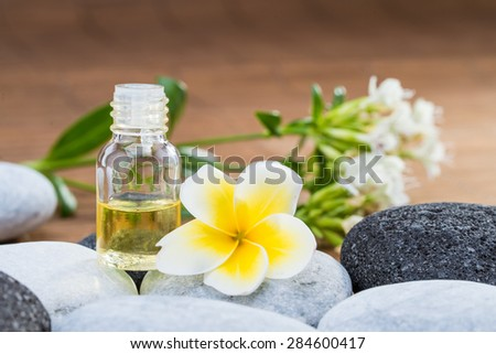 Essential Oil and flower on pebble stone with blur background glass bottle - stock photo