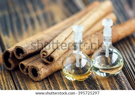 Essential oil in glass bottle with cinnamon sticks on wooden background. Beauty treatment. Spa concept. Selective focus. - stock photo