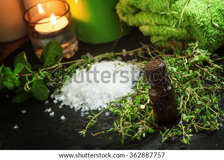 essential oil of thyme in the spa concept with sea salt, towels, burning scented candles, fresh herbs thyme, on a wet dark background, selective focus - stock photo