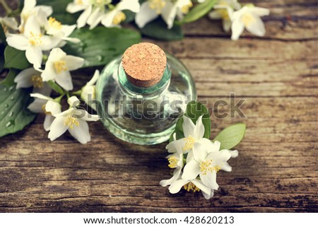 Essential oil with jasmine flower on rustic wooden table - stock photo