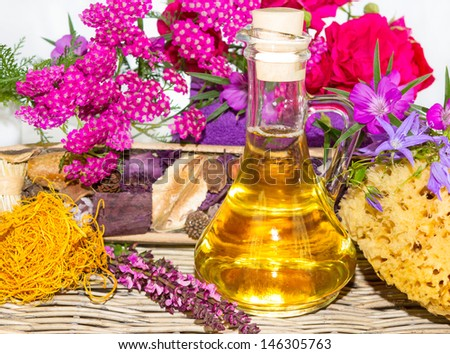 Essential oil with roses and herbs for spa - stock photo