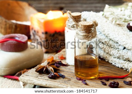 Essential Oils Bottles for Aromatherapy.Spa Setting with Soap, Towel and Anise - stock photo