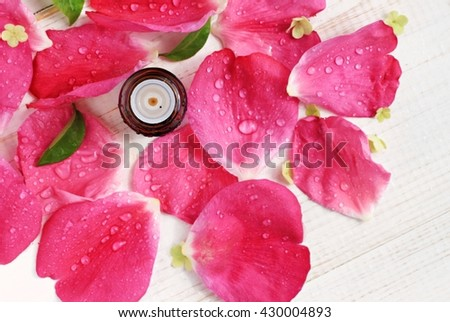 Essential rose oil bottle, pink fresh petals water-drops scattered background, top view, aromatherapy spa. Shallow focus on bottle, flowers naturally blurred. - stock photo