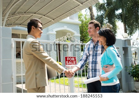 Estate agent and customer shaking their hands - stock photo