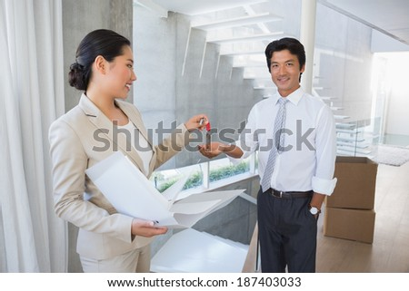 Estate agent giving house key to buyer in the hallway - stock photo