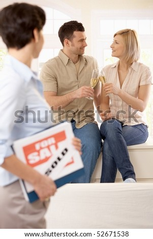 Estate agent holding for sale sign looking at celebrating couple holding champagne glasses in focus. - stock photo