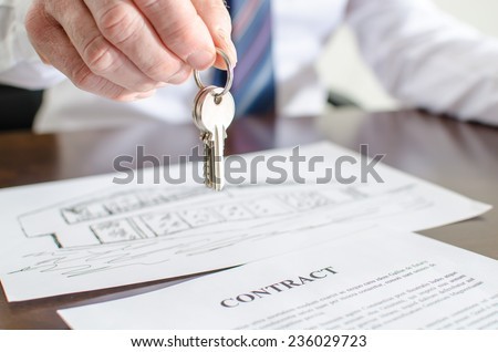 Estate agent holding house keys over a contract - stock photo