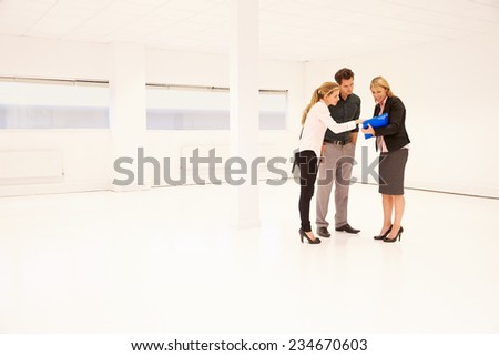Estate Agent Showing Empty Office Space To Potential Clients - stock photo