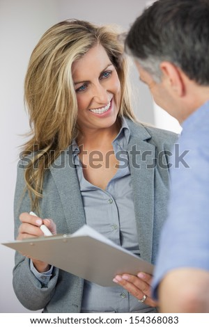 Estate agent showing lease to customer and smiling in an empty home - stock photo