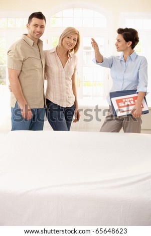 Estate agent showing young happy couple around in new house.? - stock photo