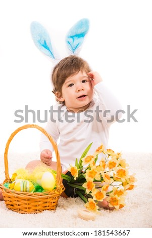 Ester bunny baby with basket with eggs and flowers sitting on carpet - stock photo