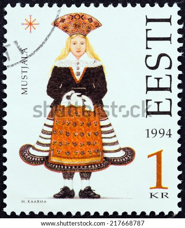"ESTONIA - CIRCA 1994: A stamp printed in Estonia from the "" Folk Costumes "" issue shows traditional clothing from Mustjala, circa 1994.  - stock photo"