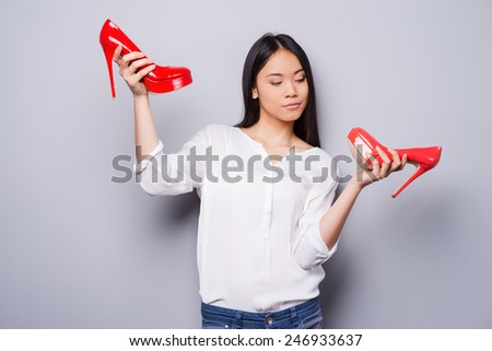 Eternal dilemma. Beautiful young Asian woman holding shoes of different colors while standing against grey background   - stock photo