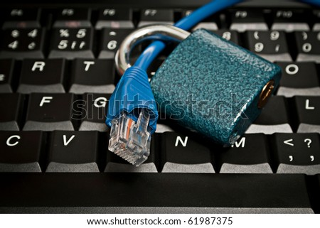 Ethernet cable on keyboard with a padlock as a metaphor for internet security, antivirus protection, firewalls and other data protection products. - stock photo