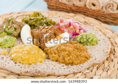 Ethiopian Feast - Injera (sourdough flatbread) with doro wat (red chicken stew), yebeg alicha (mild lamb stew), misir wat (red lentils puree), kik alicha (yellow split peas) and gomen (collard greens) - stock photo