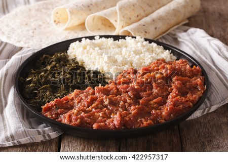 Ethiopian food kitfo: marinated beef with herbs and cheese close-up on a plate and injera. horizontal