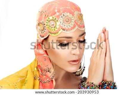 Ethnic beauty. Beautiful hindu woman with traditional clothes, jewelry, makeup and expression of greeting originally from India. Namaste - stock photo