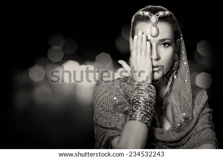 Ethnic beauty fashion. Beautiful indian woman with traditional clothes, jewelry and makeup covering half face with one hand. Monochrome portrait isolated on black with copy space - stock photo