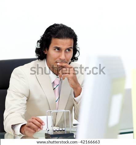 Ethnic businessman using kinetic balls in the office - stock photo