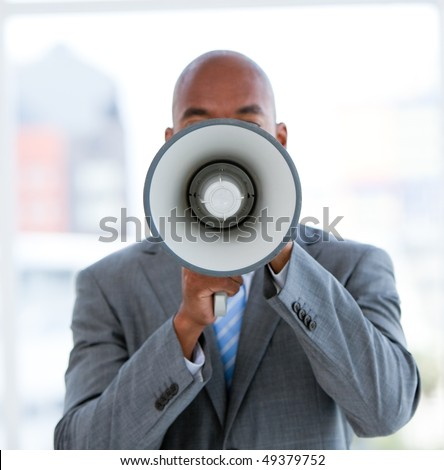 Ethnic businessman yelling through a megaphone in the office - stock photo