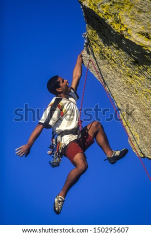 Ethnic climber dangles from his fingertips on a challenging mountain peak. - stock photo