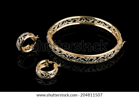 Ethnic earrings and a bracelet on black - stock photo