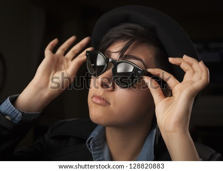 Ethnic Mixed Girl Wearing Sunglasses Against a Dark Background. - stock photo