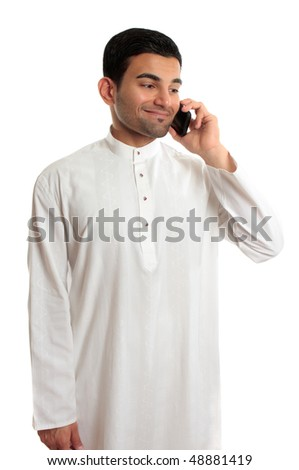 Ethnic mixed race middle eastern man in traditional dishdasha, kurta, thobe, robe, with silver buttons inlaid with rubies is chatting on a mobile phone, cellphone. - stock photo