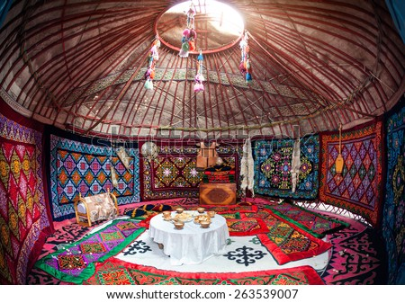 Ethnic nomadic house yurt interior with table of national food at Nauryz celebration - stock photo