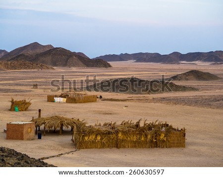 Ethnic oasis and traditional living hut of Bedouin in Arabian desert. Visiting Bedouin in Egypt - African adventure and familiarity with muslim cultural tradition. - stock photo