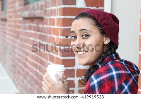 Ethnic woman drinking coffee in the morning sitting outdoors (soft focus on eyes) - stock photo