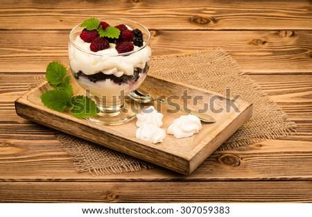 Eton mess - english traditional dessert with cream, meringues and berries served on the wooden tray.  - stock photo
