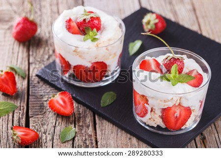 Eton Mess - Strawberries with whipped cream and meringue in a glass beaker. Classic British summer dessert.selective focus - stock photo