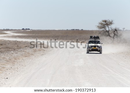 ETOSHA, NAMIBIA - OCTOBER 27 2013: Safari Truckdrives on dusty road in a year of drought at Etosha National Park, Namibia, Africa - stock photo