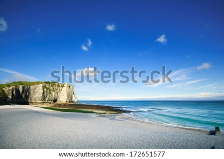 Etretat Aval cliff landmark, its beach and a blue sky. Normandy, France, Europe. - stock photo