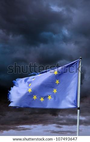 EU torn flag in stormy sky - stock photo