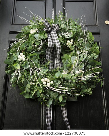 Eucalyptus Christmas wreath hung on a black door - stock photo