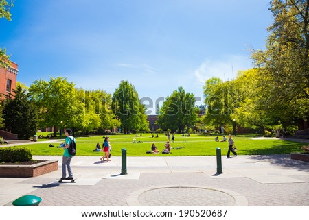EUGENE, OR - APRIL 29, 2014: Grass plaza in front of the Lillis Business School at the University of Oregon with students relaxing and sitting. - stock photo