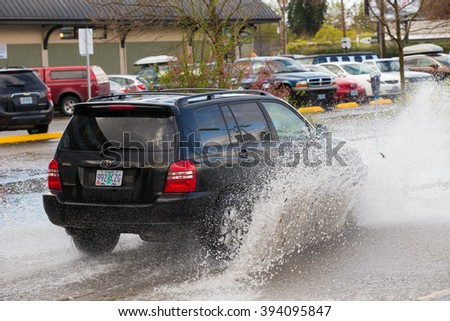 EUGENE, OR - MARCH 20, 2016: Automobile driving through a large puddle on the University of Oregon campus after torrential rainstorms moved through Eugene. - stock photo