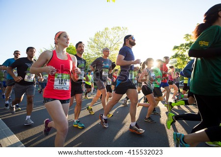 EUGENE, OR - MAY 1, 2016: Runners in a pack at the start of the 2016 Eugene Marathon, a Boston qualifying event. - stock photo