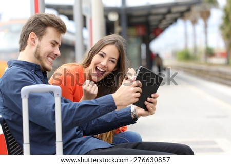 Euphoric couple watching movies or playing games in a tablet in a train station - stock photo