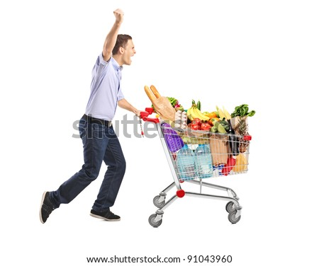 Euphoric man pushing a shopping cart full with food isolated on white background - stock photo