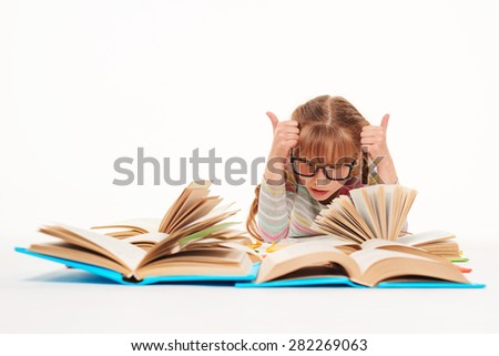 Eureka. Excited little girl lying on stomach on the floor with a lot of opened books in front of her, giving double thumbs up, over white background - stock photo