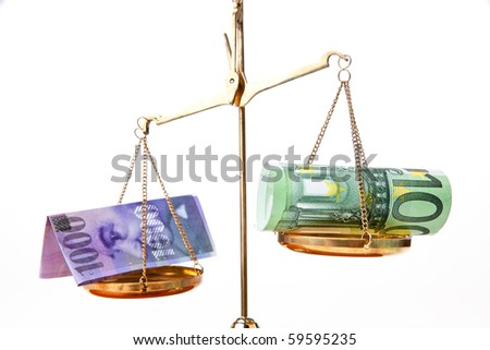 Euro and Swiss franc on a scale - stock photo