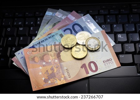 Euro banknotes and coins on laptop keyboard - stock photo