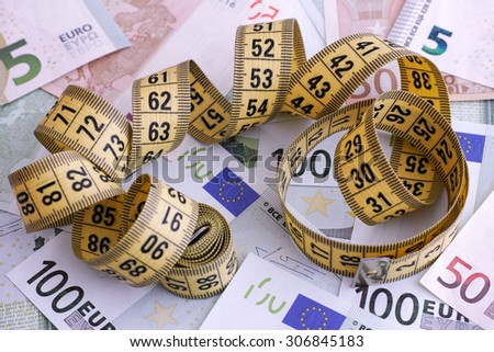 Euro banknotes and yellow tape measure. Close up. - stock photo