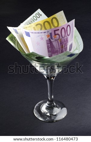 euro banknotes in cocktail glass on black background - stock photo