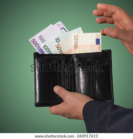 Euro banknotes in the black wallet isolated on green background. Man holding wallet with money.  - stock photo
